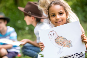 School children learning about animal species, girl holding picture of a bird