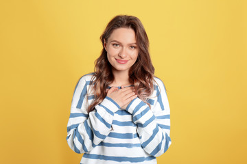 Beautiful grateful woman with hands on chest against yellow background