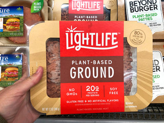 Alameda, CA - Oct 18, 2019: Grocery store refrigerator section hand holding Nightlife brand plant based ground protein. Plant based proteins can be as healthy as animal based proteins.