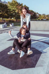 Three teenage girls of schoolgirls 12-14 years old, in summer in city, ride skateboard, happy smiling, having fun rejoicing. Weekend break. Casual clothes, warm sweaters. Emotions positive and delight