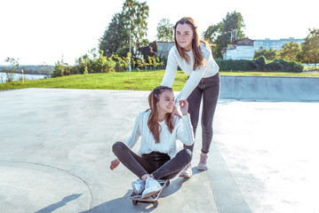 Two teenage girls, schoolgirls of 12-14 years old, in summer in city, ride skateboard, happy smiling, having fun rejoicing. Weekend break. Casual clothes, warm sweaters. Emotions positive and delight