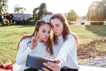 Two girls schoolgirl girlfriends 12-14 years old, taking pictures of themselves on phone, selfie portrait, recording video on social networks, air kiss, online communication in Internet application.