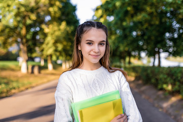Beautiful happy school girl, summer portrait in city on street in park, in hands of notebooks and folders with textbooks, resting after school in college on break. Emotions of positive and pleasure.