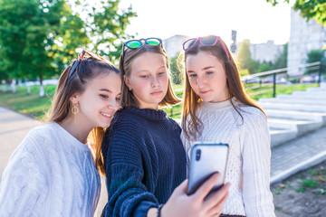 Three teenage girls schoolgirl 12-14 years old, summer city, hand smartphone, smiling happy, watching photos Internet. Selfie photo, online. Casual clothes, warm sweaters. Break school college.