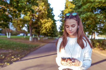 teenager girl 12-15 years old, holds mobile phone in hands, summer park, reads and writes message application, social networks Internet. Listens to music on headphones, free space for copy text.