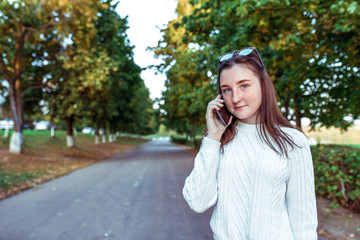 teenager girl 10-12 years old, holds smartphone in hand, listens voice message, calls mobile, summer on street park, beautiful thoughtful. Casual clothes, trees background. Free space for copy text.