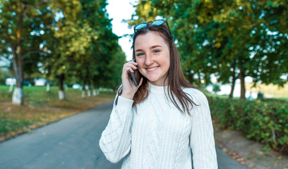 happy and joyful girl 10-12 years old, holds smartphone hand, listens voice message, calls on cell phone, summer street in park, beautiful cheerful. Emotions are fun relaxation, positive and pleasure.