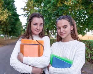 Two girls schoolgirl girlfriends 11-13 years old, summer portrait in city on street, in hands of notebooks folders textbooks, resting after school in college break. Emotions of positive pleasure.