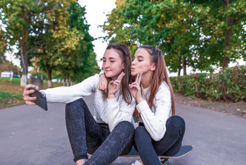 Two girls schoolgirls 12-14 years old, in summer in city park, taking selfie photo on smartphone, sitting on skateboard, casual clothes, break school and college, online official networks on Internet.