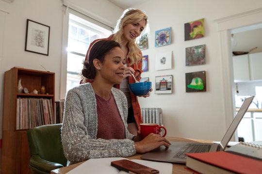 Female roommates using computer in apartment