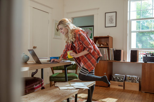 Young woman drinking coffee and working from home at laptop in dining room