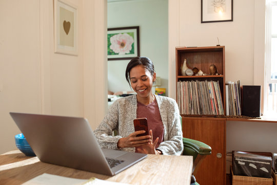 Smiling woman with smart phone working from home at laptop in apartment