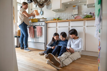 Mother cooking while children use digital tablet in apartment kitchen