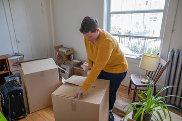 Woman packing cardboard box, moving out of apartment