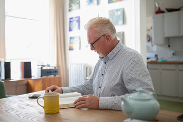 Senior man reading book and drinking tea at table