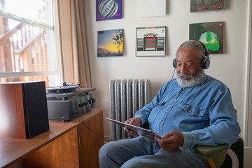 Senior man with headphones listening to music on record player