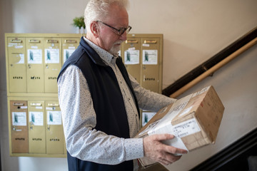 Senior man with package at apartment mailboxes