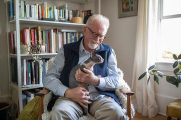 Senior man holding hairless Sphynx cat in lap