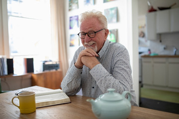 Portrait happy senior man reading book and drinking tea at table