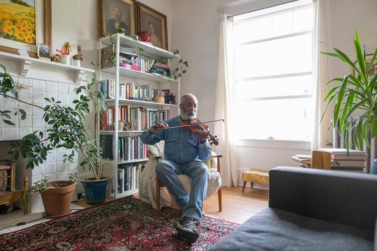 Senior man playing violin in apartment living room