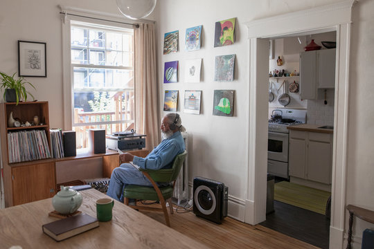 Senior man with headphones listening to music on record player in apartment living room