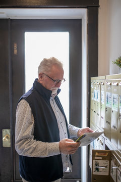 Senior man checking mailbox in apartment foyer