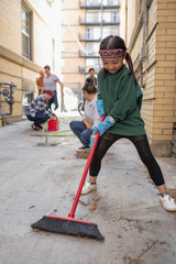Cute girl with broom helping neighbors clean apartment alley