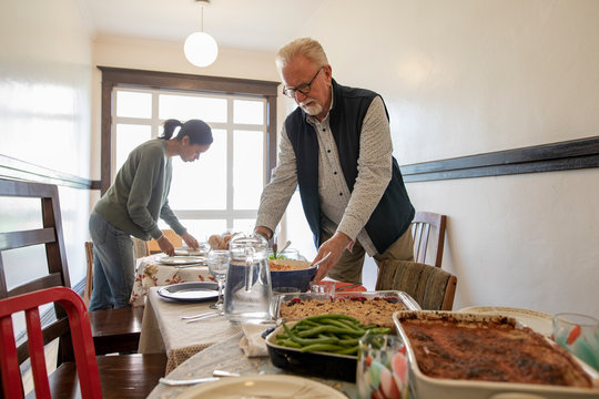 Senior man placing casserole on table for community dinner in apartment hallway