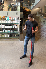 Man using smart phone and working in boutique store, holding broom