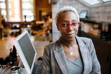 Portrait of female store owner wearing red eyeglasses smiling
