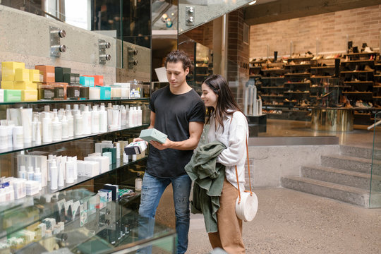 Shop assistant helping female customer choose beauty product