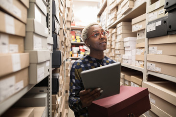 Shoe store manager using digital tablet in storeroom