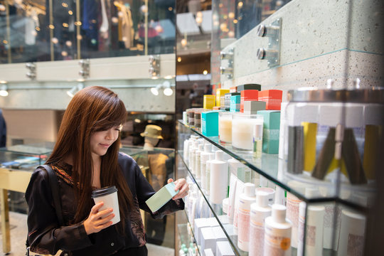 Asian woman looking at beauty product in department store