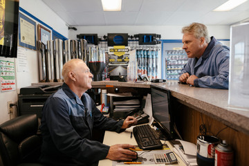 Mechanic using computer and talking to colleague in auto parts shop