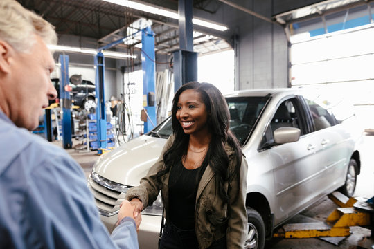 Mechanic shaking hands with female customer after car service
