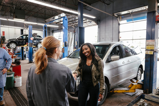Female mechanic shaking hands with customer after car service
