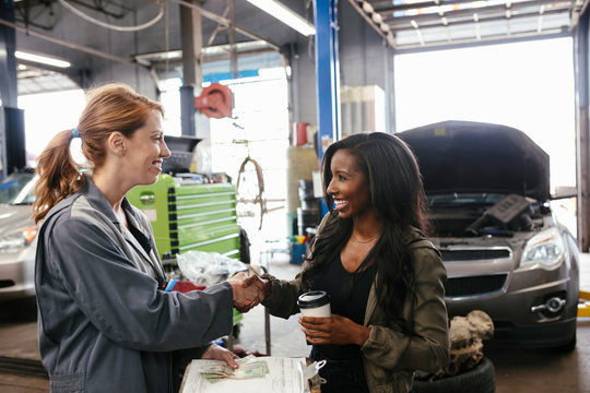 Customer shaking hands with female mechanic after car service