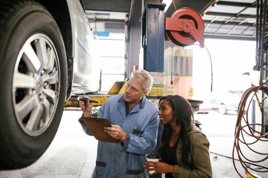 Mechanic inspecting wheel with female customer in garage