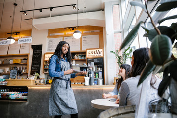 Waitress taking order from two women in cafe