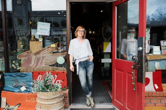 Female business owner standing in doorway of gift shop