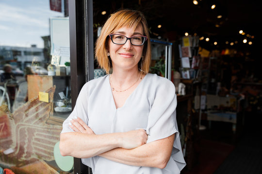 Portrait of female owner gift shop owner wearing glasses and smiling