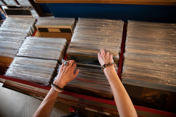 Woman searching through records in independent record store