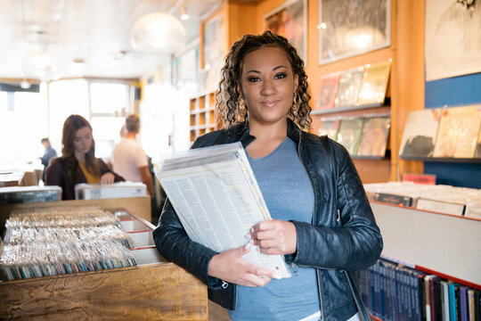 Cheerful young woman holding record in independent record store