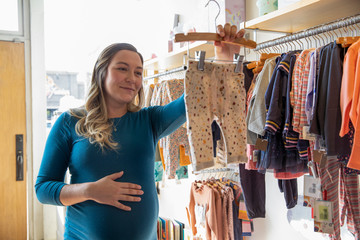 Pregnant woman looking at clothes in baby boutique with hand on belly