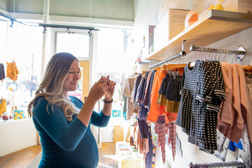 Pregnant woman photographing clothes in baby boutique