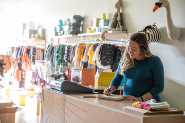 Pregnant woman working in baby boutique
