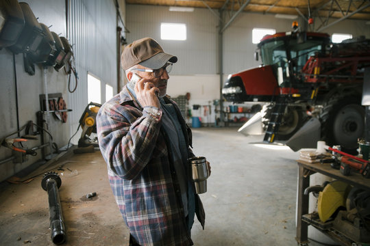 Senior male farmer drinking coffee and talking on smart phone in barn workshop