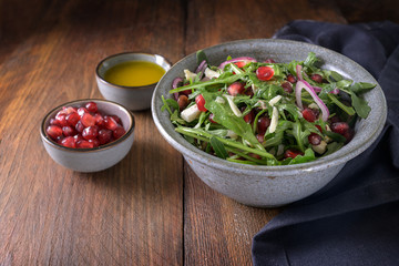 Arugula or rocket salad with pomegranate seeds and parmesan cheese in a bowl on a dark rustic wooden table