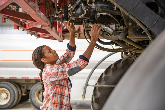Female farmer fixing tractor