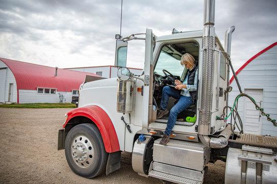 Female senior farmer with clipboard inside semi truck on farm